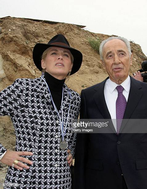 Actress Sharon Stone stands with former Israeli Prime Minister Shimon Peres while visiting Israeli Jewish and Arab children at a tennis center March...