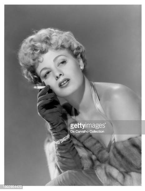 Actress Shelley Winters holds a cigarette in a glamourous atmosphere in a publicity shot from the late 1940's, United States.