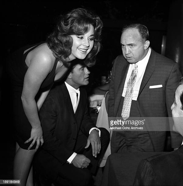 Actress Sherry Jackson chats with an unidentified man as LA gangster Mickey Cohen looks on at a nightclub in 1959 in Los Angeles California