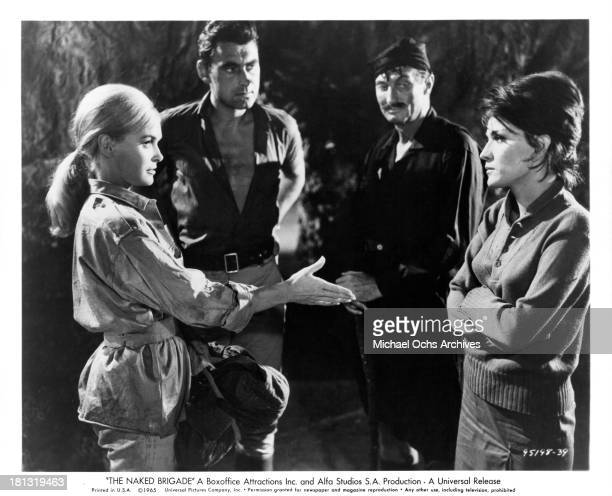 Actress Shirley Eaton actor Ken Scott and John Holland with actress Mairi Hronopoulou on set of the Universal Pictures movie The Naked Brigade in 1965
