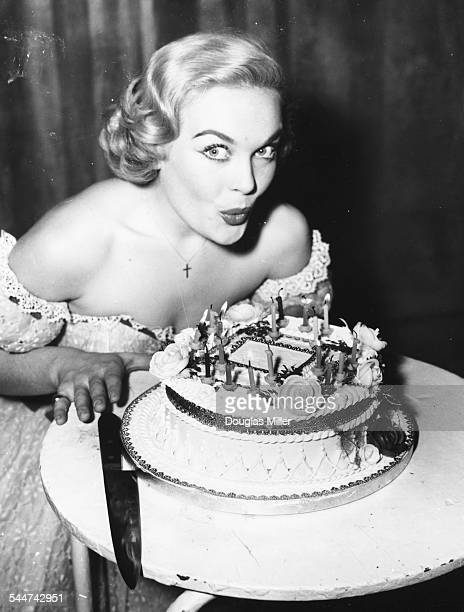 Actress Shirley Eaton blowing the candles out on her birthday cake as she celebrated her 18th birthday behind the scenes at the London Palladium...