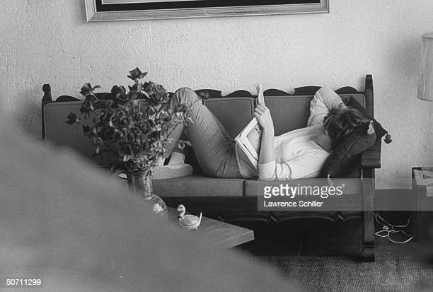 Actress Shirley MacLaine lying on couch absorbed in magazine.