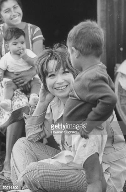 Actress Shirley MacLaine sitting on ground w. Legs crossed being amused by little boy as unident. Woman sits in bkgrd. W. Child on her lap.