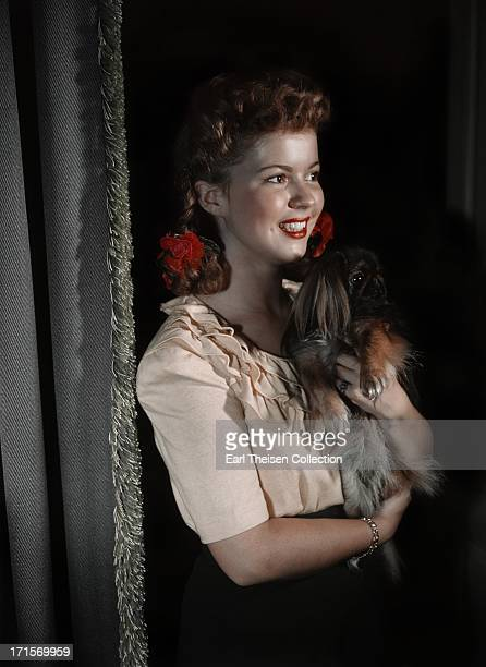 Actress Shirley Temple poses for a photo with her dog at home in 1944 in Los Angeles California