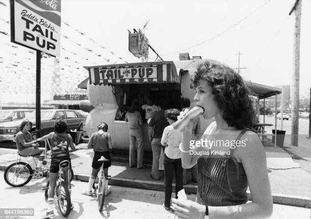 Actress Sigourney Weaver eats a hot dog in front of the Tail o' the Pup hot dog stand on La Cienega Boulevard in Los Angeles California