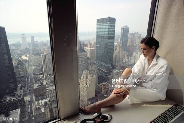 Actress Sigourney Weaver poses in a window overlooking other skyscrapers in New York