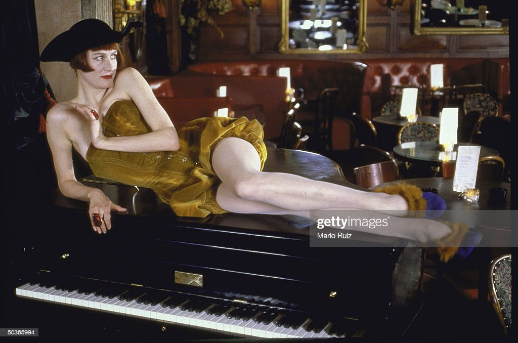 Actress, singer, and club owner Nell Campbell posing on top of a piano in a revealing, strapless getup and a Paul Revere style hat her club, Nell's.