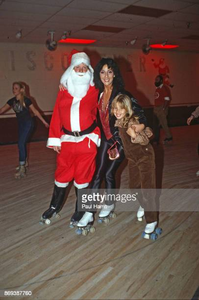 Actress singer Cher roller skates with Father Christmas and her daughter Chastity from her marriage to Sonny Bono at a Christmas roller skating party...