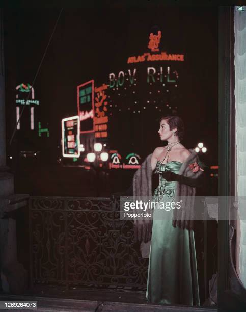 Actress Sonia O'Shea wears a Lucca lamb stole over a green satin strapless evening dress as she views the lights of Piccadilly Circus from a balcony...