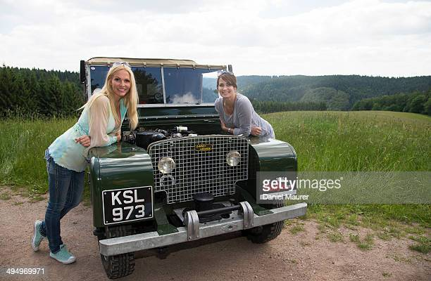 Actress Sonya Krauss and actress Anja Kling pose on a Landrover Series 1 during the Ralley One on May 31, 2014 in Durbach, Germany.