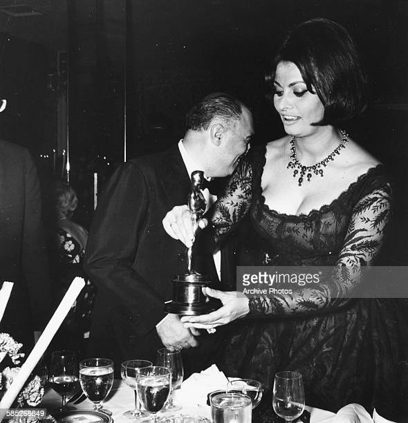 Actress Sophia Loren with her Best Actress Oscar for the film 'Two Women' with her husband Carlo Ponti at a party held by Joe Levine where she...