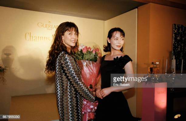 Actress Sophie Marceau is given flowers by Japanese actress Yoko Shimada during an event in Tokyo to promote a new perfume Champs Elysses Marceau is...