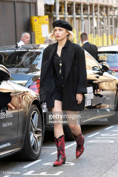 Actress Sophie Simnett wears a Bite London jacket shirt and shorts black beret and Jessie Western boots during London Fashion Week September 2019 on...