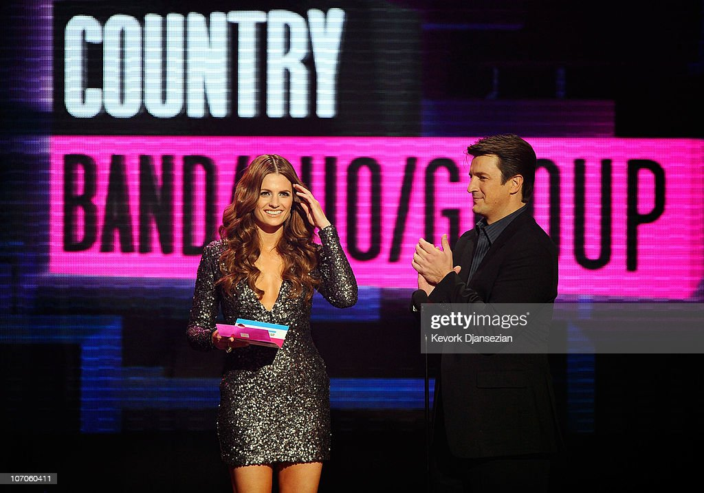 Actress Stana Katic (L) and actor Nathan Fillion speak onstage during the 2010 American Music Awards held at Nokia Theatre L.A. Live on November 21, 2010 in Los Angeles, California.