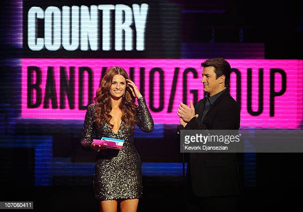 Actress Stana Katic and actor Nathan Fillion speak onstage during the 2010 American Music Awards held at Nokia Theatre LA Live on November 21 2010 in...