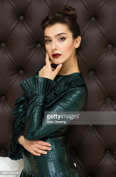 Actress Stella Egitto poses in her hotel room while wearing a dark green dress by Blumarine and heels by Alexandre Birman during Milan Fashion Week...