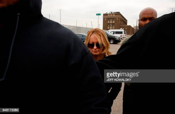TOPSHOT Actress Stephanie Clifford who uses the stage name Stormy Daniels heads to the Detroit Police Department's 4th Precinct flanked by her body...