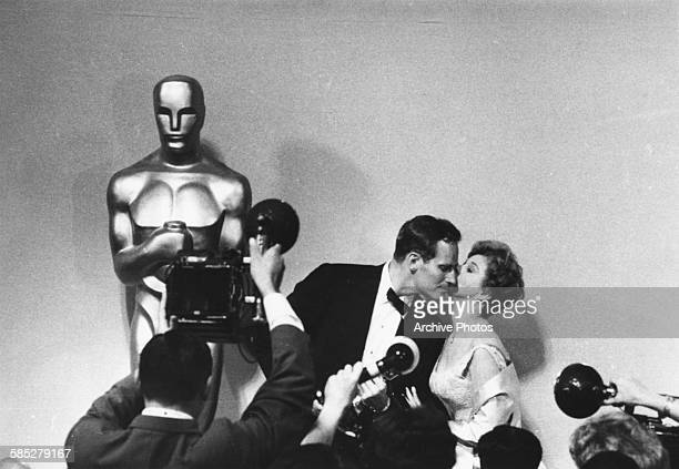 Actress Susan Hayward kissing Charlton Heston on the cheek in front of a bank of photographers after he received his Oscar for the film 'Ben Hur' at...