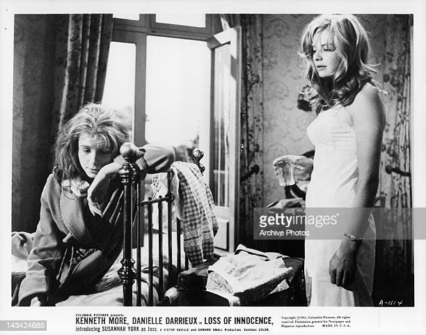 Actress Susannah York holding a glass as Jane Asher leans against bedpost in a scene from the film 'Loss Of Innocence' originally titled 'The...