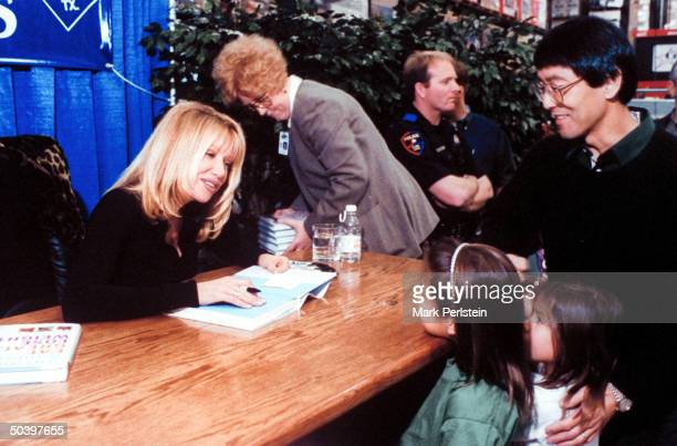 Actress Suzanne Somers autographing copies of her new book EAT GREAT LOSE WEIGHT while chatting w two tiny fans outside of a Sam's Club in Texas