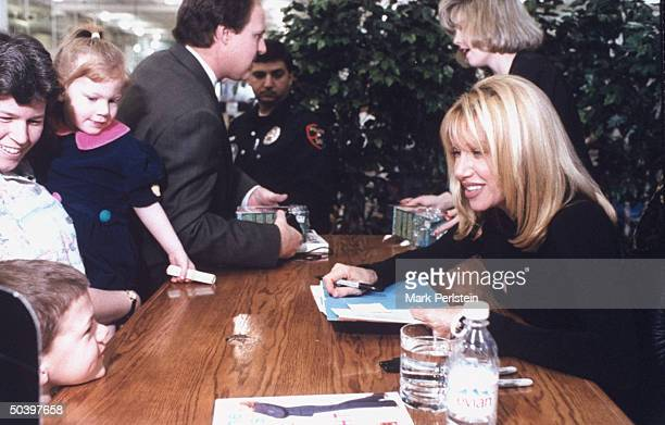 Actress Suzanne Somers autographing copies of her new book EAT GREAT LOSE WEIGHT while chatting w a tiny fan outside of a Sam's Club in Texas