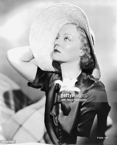 Actress Tallulah Bankhead in a promotional shot for Paramount Pictures wearing a black satin dress and a wide brimmed hat 1932
