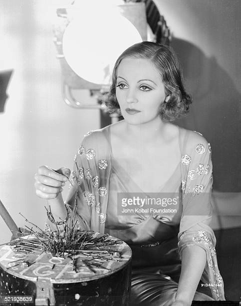 Actress Tallulah Bankhead in a promotional shot for Paramount Pictures wearing a nightgown and playing a board game 1932