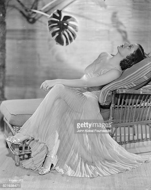 Actress Tallulah Bankhead in a promotional shot for Paramount Pictures lying down and wearing a white pleated dress 1932