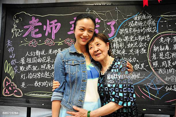 Actress Tang Wei in pregnancy poses with teacher in her primary school on May 29 2016 in Hangzhou Zhejiang Province of China