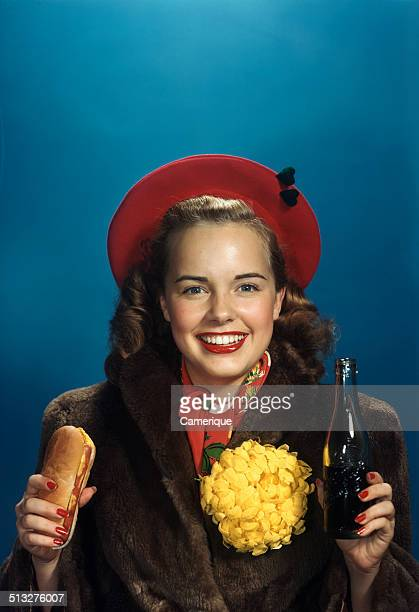 Actress Terry Moore holding hot dog and bottle of soda pop wearing fur coat and big yellow homecoming chrysanthemum Los Angeles California 1949