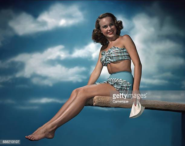 Actress Terry Moore in a plaid 2piece bathing suit sitting on a diving board Los Angeles California 1950s