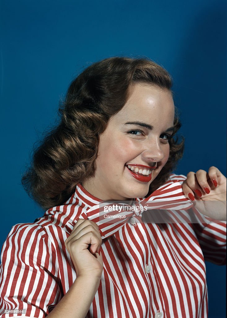 Actress Terry Moore In Red Striped Blouse Tugging On Bowtie : News Photo