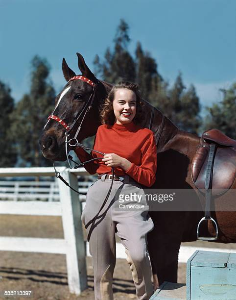 Actress Terry Moore standing with her black horse Los Angeles California 1950s