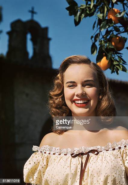 Actress Terry Moore wearing off the shoulder lace blouse posing by orange tree church cross steeple in background Los Angeles California 1949
