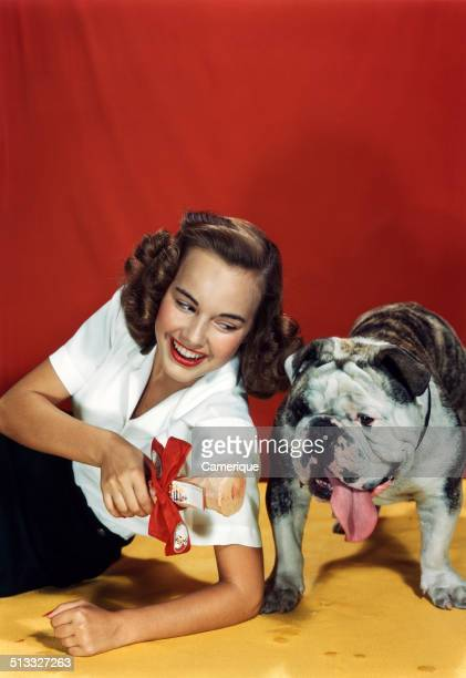 Actress Terry Moore with a bulldog and bone Los Angeles California 1949