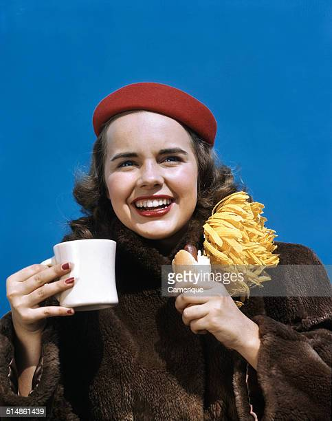 Actress Terry Moore with a hot dog and hot chocolate go team Los Angeles California 1949