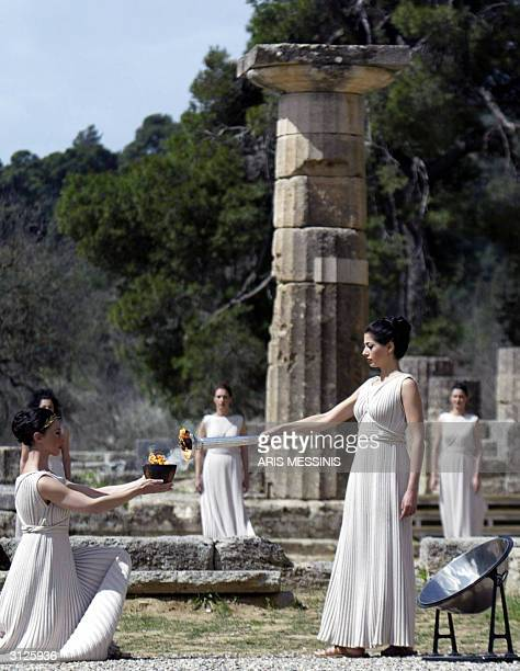 Actress Thalia Prokopiou acting as high priestess gives the flame to another priestess in the ancient sanctuary where the Olympic Games were started...