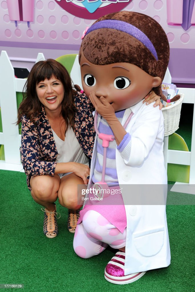 Actress Tiffani Thiessen (L) and Doc McStuffins attend the Doc Mobile Tour at the Disney Store on August 21, 2013 in New York City.