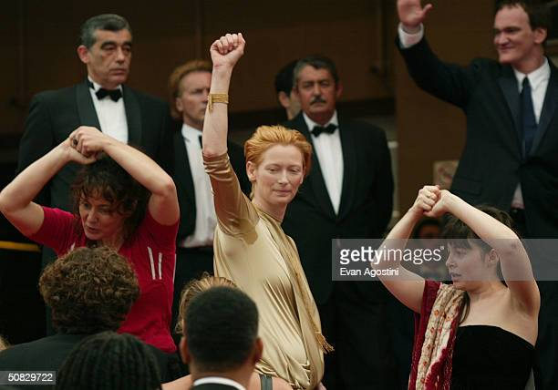 Actress Tilda Swinton gestures in support of protesting French parttime film and theatre industry workers as she walks up the festival palace stairs...