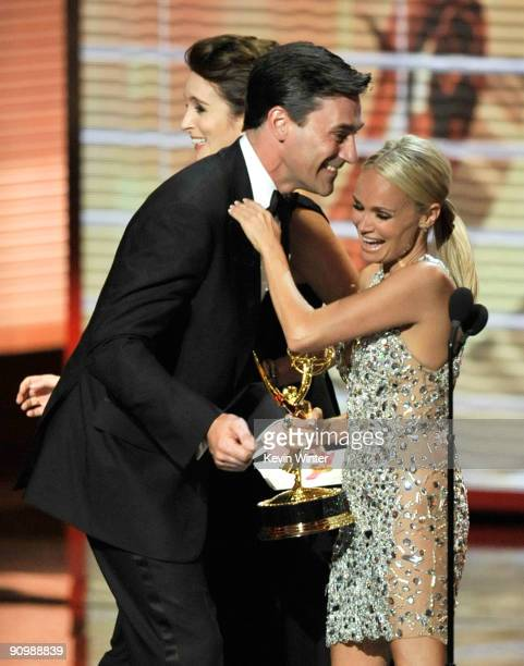 Actress Tina Fey and actor Jon Hamm present the Outstanding Supporting Actress in a Comedy Series award to actress Kristin Chenoweth onstage during...