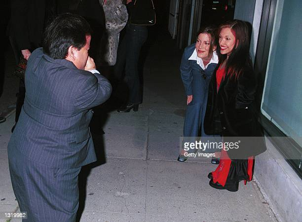 Actress Tori Spelling left poses with actress Bridgette Powers while actor Gary Friedkin takes a picture during a party and final shoot for Joe Head...