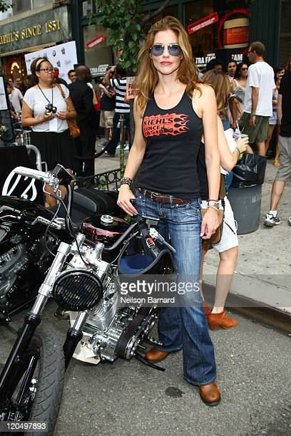 Actress Tricia Helfer arrives on a BMW motorcycle at Kiehl's LifeRide for amfAR Block Party at Kiehl's Since 1851 New York Flagship Store on August 6...