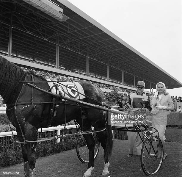 Actress Tuesday Weld poses by a jockey after a harness race during a horse race in Los AngelesCA