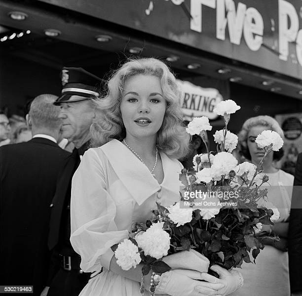 Actress Tuesday Weld poses with a bouquet of flowers during her movie premiere of The Five Pennies in Los AngelesCA