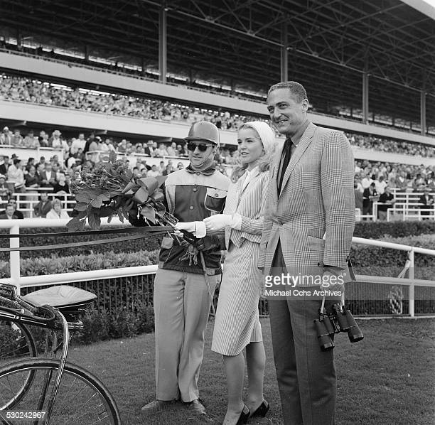 Actress Tuesday Weld poses with a jockey after a harness race in Los AngelesCA