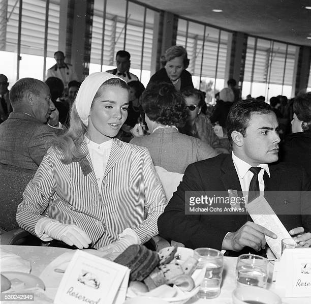 Actress Tuesday Weld with actor John Saxon attend a horse race in Los AngelesCA