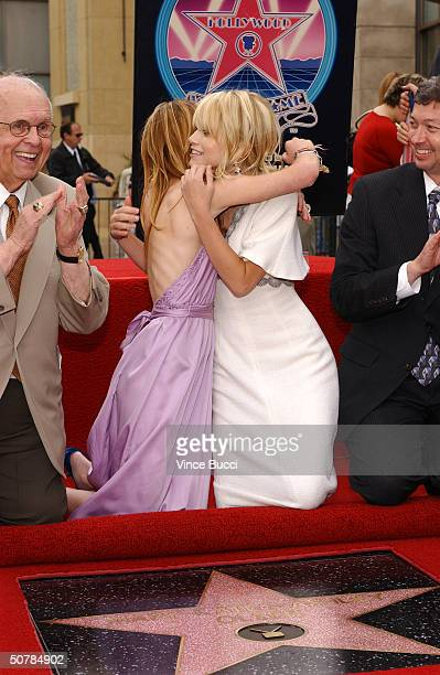 Actress twins Ashley and MaryKate Olsen embrace as they attend the ceremony honroing them with a star on the Hollywood Walk of Fame on April 29 2004...