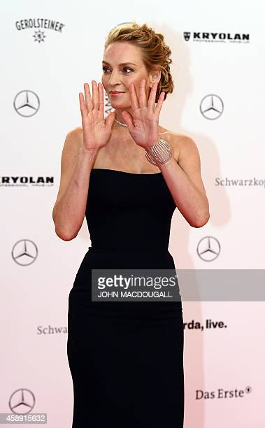 US actress Uma Thurman waves as she arrives for the Bambi awards on November 13 2014 in Berlin The Bambis are the main German media awards AFP PHOTO...