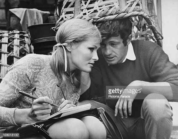 Actress Ursula Andress pictured holding a pen and pad as she listens to actor JeanPaul Belmondo who crouches beneath a large wicker basket circa 1965...