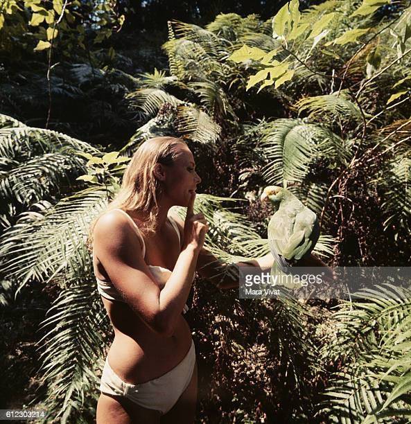 Actress Ursula Andress poses with a parrot during the filming of Dr No in Jamaica 1962